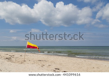 Red and yellow swimming area flag at Tisvilde beach in Denmark. - stock photo