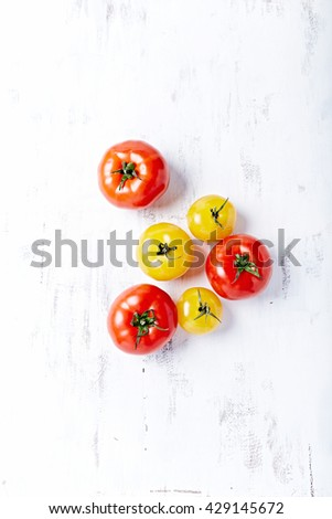 Red and Yellow Tomatoes on a Wooden Background - stock photo