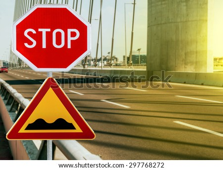 Red and yellow triangular warning road sign with STOP sign a warning of a bumpy road ahead on a rod on bridge on sunny day - stock photo