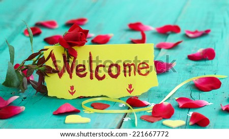 Red and yellow welcome note card with red flower, rose petals and hearts on antique teal blue wood table - stock photo