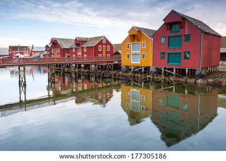 Red and yellow wooden houses in coastal Norwegian fishing village - stock photo
