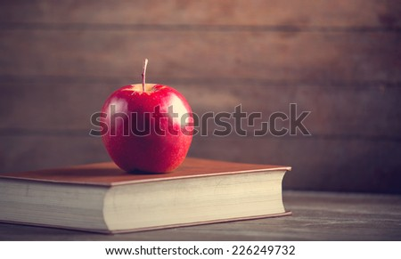 Red apple and book on a table. - stock photo