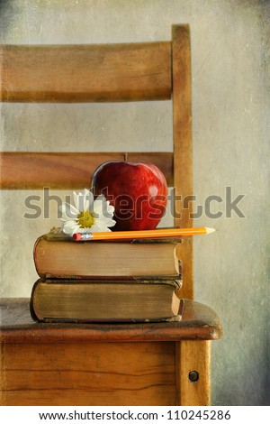 Red apple and books on old school chair - stock photo