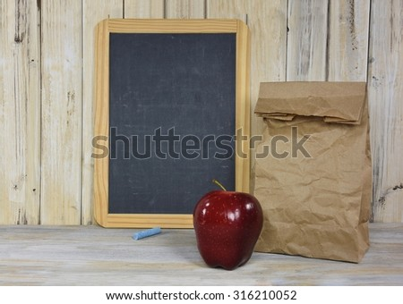red apple and brown paper sack with black chalkboard on whitewashed wood - stock photo