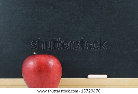 Red apple and chalkboard with chalk - stock photo