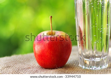Red apple and glass of water.