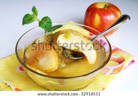 Red apple and green rhubarb fruit compote or sweet stewed fruits in a glass cup with a tea-spoon on a napkin of different colors on a white background - stock photo