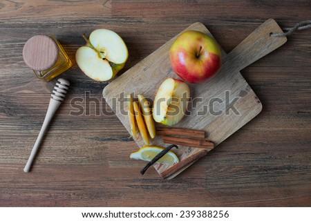 red apple and honey on the kitchen table top view (cinnamon, vanilla, lemon) - stock photo