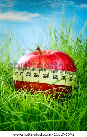 Red apple and measuring tape on the green grass. - stock photo