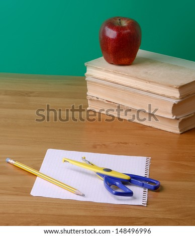 Red apple and scissors on pile of books - stock photo