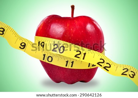 Red apple and yellow measuring tape to symbolize an healthy diet and body weight control. - stock photo