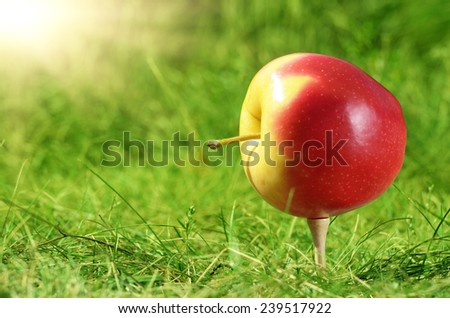 Red apple being set on wooden golf tee - stock photo