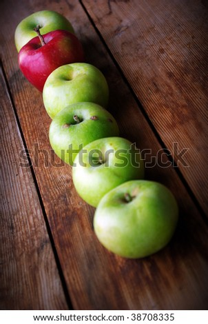 red apple between green apples on wooden surface - stock photo