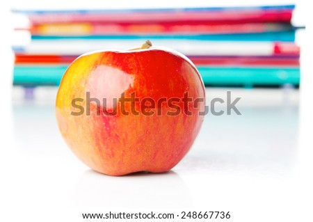 Red apple closeup and textbooks - stock photo