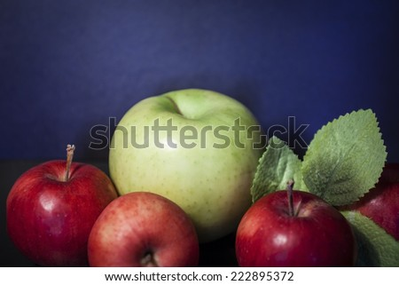 red apple contrast green foliage leaf on a blue background - stock photo