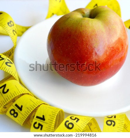 red apple,fruits for weight loss, a measuring tape, diet, weight loss - stock photo