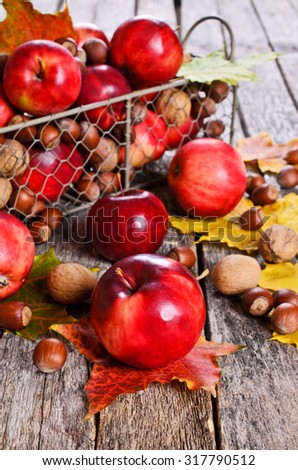 Red Apple on a background of nuts and maple leaves on wooden surface