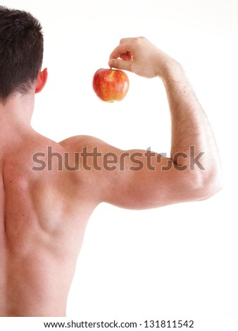 Red Apple on Man Bicep Muscle isolated on white. Athletic sexy male body builder holding - stock photo