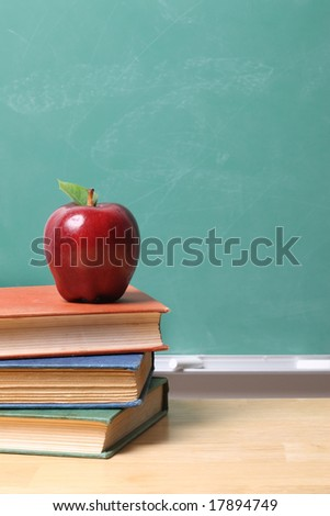 Red apple on stack of school books - stock photo