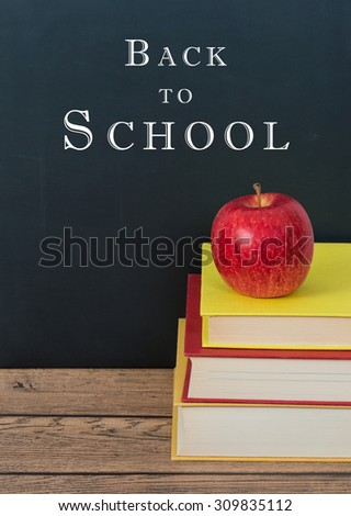 Red apple on the stack of books. Chalkboard background with Back to School text.