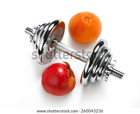 Red apple, orange citrus and dumbbell  - stock photo