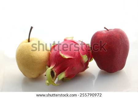 red apple pear and pitaya on white background
