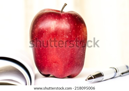 Red apple placed on a notebook - stock photo