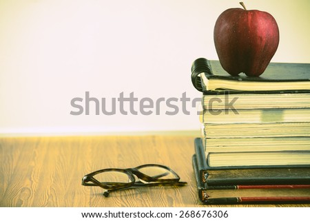 red apple resting on the book  with glasses and magnifying glass .cross process photo style - stock photo