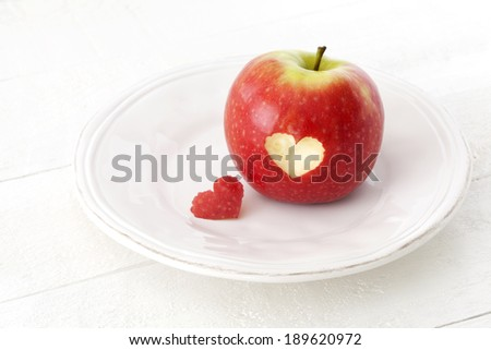 Red apple with a heart shaped cut-out on a plate