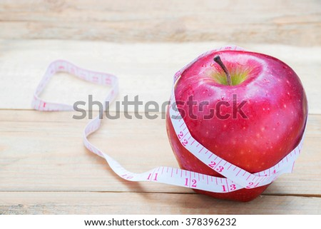Red apple with a measure tape on the wood background - stock photo