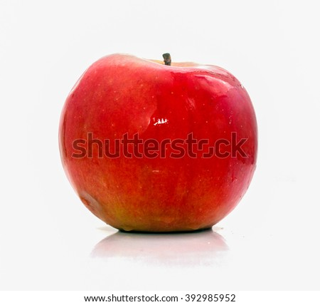 Red apple with green tint on white background