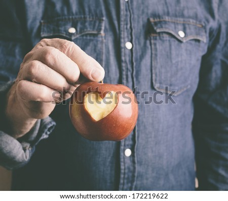 red apple with hand of man - stock photo