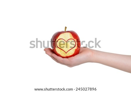 red apple with heart design in open hand isolated white background
