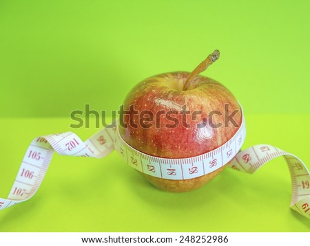 Red apple with measuring tape - stock photo