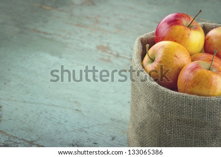 Red apples in a burlap sack with vintage editing and copy space - stock photo