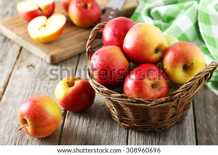 Red apples in basket on grey wooden background - stock photo
