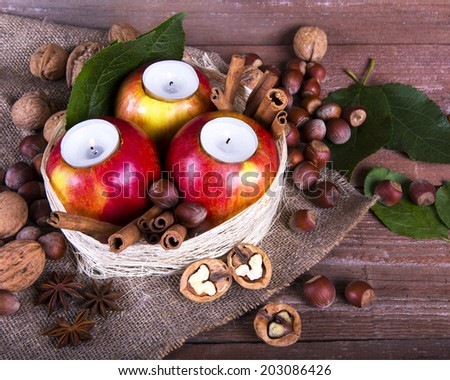 red apples with candles, cinnamon, nuts - stock photo