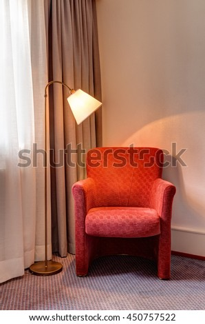 Red armchair and floor lamp in the corner of the room.