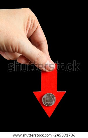 Red Arrow in a Hand with Russian Ruble Down on the Black Background - stock photo
