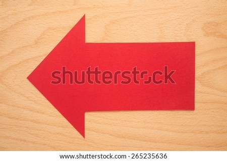 Red arrow sign on a wooden background