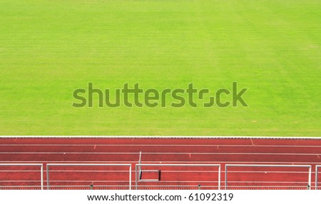 Red athletics track with green field - stock photo