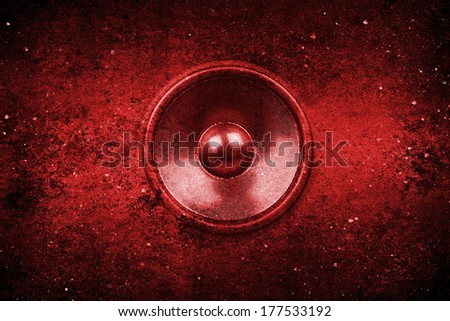 Red audio speaker on a rough grunge wall background