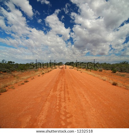 Red Australian Rural Road with Cloudy Blue Skies - stock photo