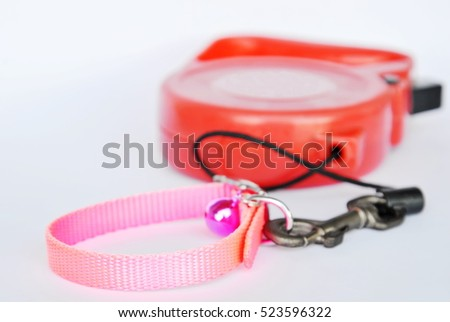 red automatic leash and pink nylon pet collar on white background