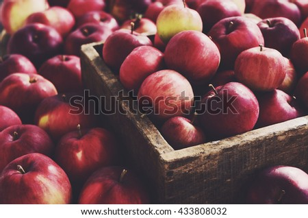 Red autumn apples in farmhouse style wooden crate - stock photo
