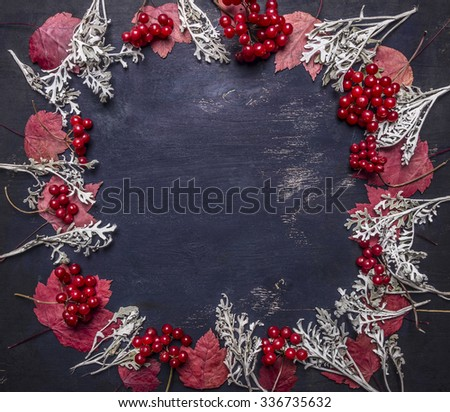 Red autumn leaves and berries Viburnum, lined frame space for text on wooden rustic background top view