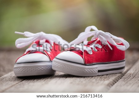 Red baby sneakers on wooden background - stock photo