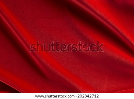 red background photo of wavy folds of silk satin or velvet material or luxurious red background with elegant curves of red material for Christmas - stock photo