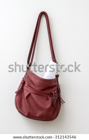 Red bag hanging  over a white wall, close up - stock photo