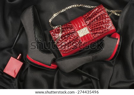 Red bag, shoes and perfume lying on black satin as background - stock photo